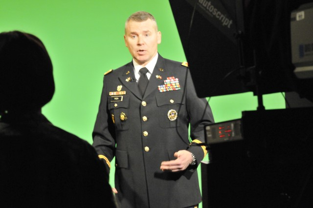 Col. Edward Prem, chief of the Functional Management Division, G-1, tells television reporter Staff Sgt. Jennifer Anderson about the Integrated Personnel and Pay System-Army first release which will be available this fall.