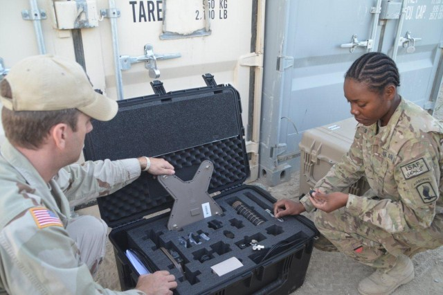 David Gage, logistics management specialist with the Wolfhound team, shows each component in the Wolfhound Handheld Threat Warning System to Cpl. Shaniece S. Bolden, supply sergeant, Headquarters and Headquarters Company, 173rd Airborne Brigade Combat Team, as he issues new equipment to the unit. (Photo by Summer Barkley, 401st AFSB Public Affairs)