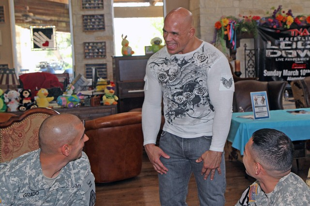 "FORT SAM HOUSTON, Texas "" Shawn ""SuperMex"" Hernandez, a professional wrestler with Total Nonstop Action Wrestling, jokes about ""locking down"" Spc. Steven Grado (left) and Spc. Jesus Zarzoa, both wounded warriors while visiting the Warrior and Family Support Center March 5. Hernandez said he wanted to visit the wounded warriors because of his dad. ""My father was a Green Beret for 30 years,"" said Hernandez. ""He was my hero growing up; so any time I can give back to Soldiers, I am down with it."" Hernandez and Velvet Sky, a fellow TNA wrestler, are in town for a ""Lockdown"" wrestling match March 10 at the Alamodome in San Antonio."