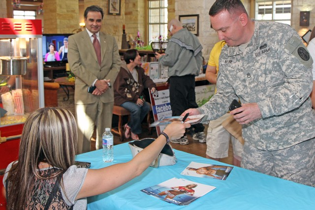 "FORT SAM HOUSTON, Texas "" Staff Sgt. Patrick Ryan, a squad leader with Company B, Warrior Transition Battalion, receives a signed photo March 5 from Velvet Sky, a professional wrestler with Total Nonstop Action Wrestling. Velvet Sky and Shawn ""SuperMex"" Hernandez, a fellow TNA wrestler, signed autographs at the Warrior and Family Support Center after touring the facility. Hernandez, whose father was a career Soldier with 30 years, said visiting the WFSC was an eye-opener because ""you don't really think about the casualties of war; seeing them is important."" The wrestlers are in town for a wrestling match March 10 at the Alamodome in San Antonio."