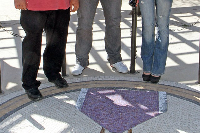 "FORT SAM HOUSTON, Texas "" Shawn ""SuperMex"" Hernandez and Velvet Sky, both professional wrestlers with Total Nonstop Action Wrestling, admire the Purple Heart mosaic with Charles Domingez, the facility manager for the Warrior and Family Support Center, during a tour of the facility March 5. The wrestlers, who are in town for a local wrestling match March 10 at the Alamodome in San Antonio, signed autographs at the Center after their tour."