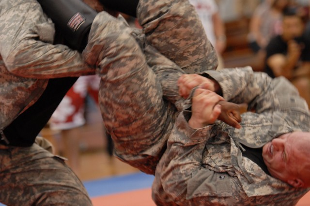 Micheal Van Horn, of the 9th Mission Support Command, attempts a straight arm bar before losing to his opponent, John Goff, from the 2nd Squadron, 14th Cavalry Regiment, and winner of the Heavy Weight Class, at the second annual All-Island Army Combatives Tournament, at the Fort Shafter (Hawaii) Physical Fitness Center, March 2-3, 2013.