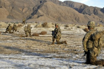 Soldiers with Bravo Company, 2nd Battalion, 23rd Infantry Regiment rest and provide security while waiting their turn to cross a creek near an Afghan village March 3 during Operation Southern Fist III in the district of Spin Boldak, Kandahar province...