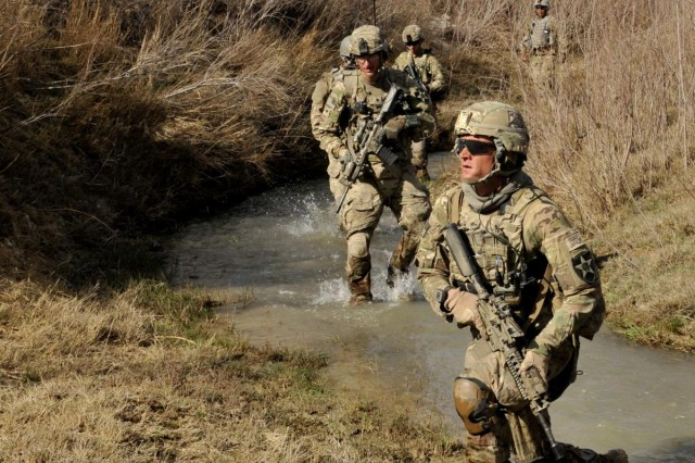 Soldiers with Bravo Company, 2nd Battalion, 23rd Infantry Regiment, approach a suspected weapons cache during Operation Southern Fist III, March 3, in the district of Spin Boldak, Kandahar Province, Afghanistan. The soldiers enabled the Afghan Border Police and Afghan National Army to search for weapons caches and eliminate infiltration routes. (U.S. Army photo by Staff Sgt. Shane Hamann, 102nd Mobile Public Affairs Detachment.)