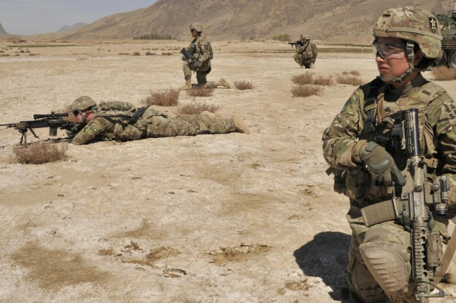 Staff Sgt. Claudia Caberoherbas, from Los Angeles, Calif., Female Engagement Team 6 and soldiers with Bravo Company, 2nd Battalion, 23rd Infantry Regiment, perform security outside a village with a suspected weapons cache March 3, in Kandahar Province, Afghanistan. The soldiers assisted the Afghan Border Police to meet with villagers and gather information. (U.S. Army photo by Staff Sgt. Shane Hamann, 102nd Mobile Public Affairs Detachment.)