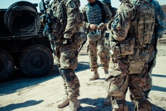 U.S. Army Capt. Derek Knapp, left, and Lt. Col. Kenneth Sheidt, right, both with Security Force Assistance Team 10, 4th Stryker Brigade Combat Team, 2nd Infantry Division, wait on an Afghan counterpart while on patrol in Kandahar province, Afghanista...