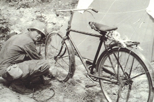 President Barack Obama announced March 11, 2013, that Chaplain (Capt.) Emil J. Kapaun will be awarded the Medal of Honor posthumously, April 11, for his actions leading up to his capture as a prisoner of war in North Korea. Here, Kapaun finds a bicycle to get around the battlefield after his jeep was destroyed by a landmine.