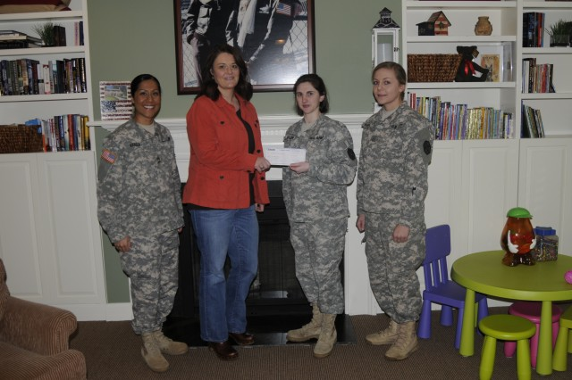 Soldiers of the 654th Regional Support Group present a check for $654 to the Fisher House at Joint Base Lewis-McChord, Wash. From left, Master Sgt. Brenda Araiza; Jodi Land, manager of Fisher House; 1st Lt. Bethany Garbarini, commander of Headquarters and Headquarters Detachment, 654th RSG; and Pfc. Ashley Burcell.