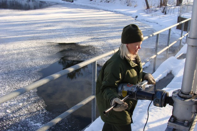 Mary Kay Larson, Gull Lake Recreation Area park manager, operates the dam during a gate change.