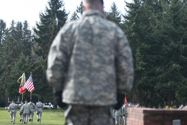 U.S. Army Lt. Col. Thomas Gordon Jr., back to camera, the incoming commander of the 2nd Battalion, 17th Field Artillery Regiment, looks on as the unit's colors are retired during a change of command ceremony at Joint Base Lewis-McChord, Wash., March 7, 2013.  (U.S. Army photo by Staff Sgt. Bryan Dominique/Released)