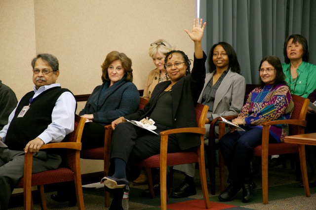 Juanita Sales-Lee, supervisory attorney, U.S. Army Space and Missile Defense Command/Army Forces Strategic Command, raises her hand in response to a trivia question during the command's Women's History Month celebration at SMDC's Redstone Arsenal headquarters March 12.