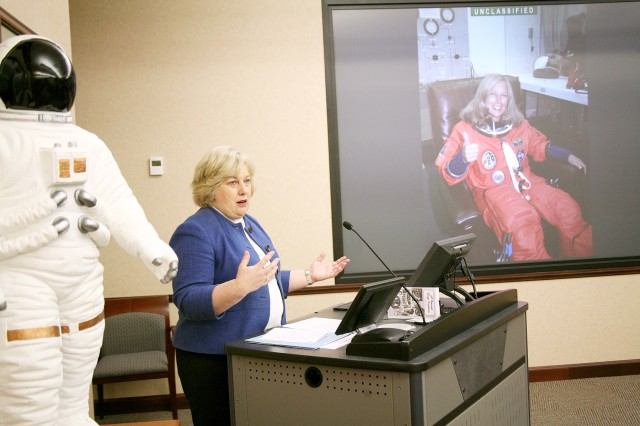 Former astronaut Jan Davis, vice president and deputy general manager of Jacobs Engineering and Science Services and Skills Augmentation Group, speaks to U.S. Army Space and Missile Defense Command/Army Forces Strategic Command employees during the command's Women's History Month celebration at SMDC's Redstone Arsenal headquarters March 12. On the screen in the background is a photo of Davis taken during the time that she served as an astronaut.