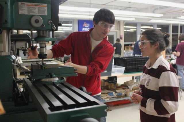 """A student with the Newton robotics team that is participating in the FIRST Robotics Competition receives guidance from a mentor in operating machining equipment. The acronym FIRST means """"For Inspiration and Recognition of Science and Technology."""""""