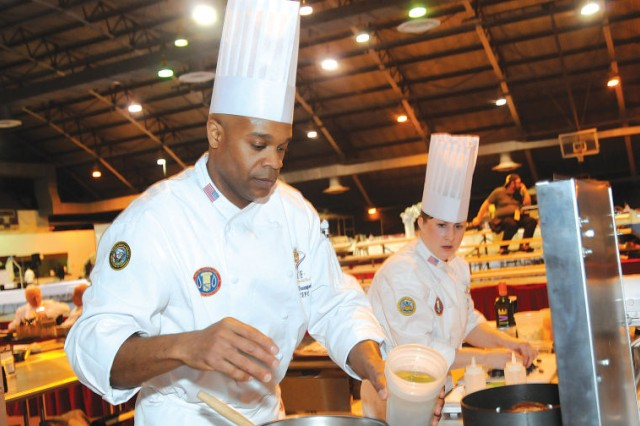 Navy Senior Chief Petty Officer Derrick Davenport and Sgt. Sarah Deckert hustle to prepare dishes during the international event of the Military Culinary Arts Competitive Training Event, March 6, 2013, at the Post Field House on Fort Lee, Va. The two, members of the U.S. Army Culinary Arts Team, earned a gold medal and the top spot in the category, beating out Germany, Canada and France.