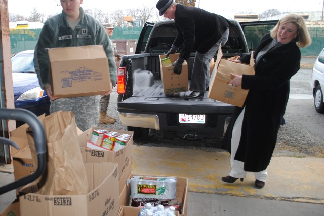 "Capt. Sean Kwoun (left), 722nd Contingency Contracting Team, and Cheryl Gloor (right), contract specialist with the Tenant Division, both at Aberdeen Proving Ground, Md., unload boxes of food in support of the APG-wide ""Harvest for the Hungry"" food drive."