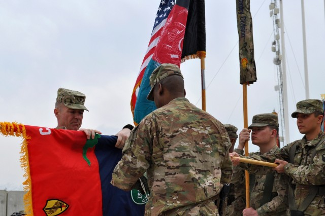 Maj. Gen. James C. McConville and Command Sgt. Maj. Alonzo J. Smith, the command team of 101st Airborne Division (Air Assault) and Combined Joint Task Force-101, unfurl the unit flag during a transfer-of-authority ceremony at Bagram Airfield, Afghanistan, March 14, 2013. The 101st Airborne Division assumed control of Regional Command-East from the 1st Infantry Division.