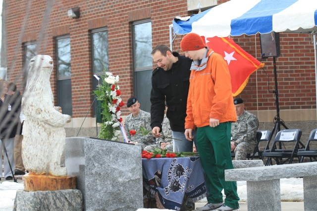Jaye Lindsay, left, and John Sechser, both former Polar Bears, place a red rose at the monument of their fallen comrades Monday during a remembrance ceremony at 4th Battalion, 31st Infantry Regiment,2nd Brigade Combat Team headquarters on Fort Drum. The ceremony commemorated the 10th anniversary of a Black Hawk crash that claimed the lives of 11 Soldiers.