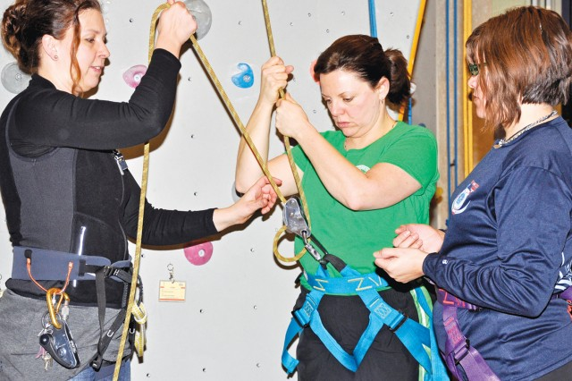 Manager Petra Ehrenberger demonstrates rope safety with the held of V Corps spouses Monica Brown (center) and Amber Heffron (right) at the T-Hall Indoor Rock Climbing in Frankfurt, Germany.