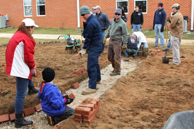 Soldiers from the Basic Officer Leaders Course help construct the outdoor classroom at Rucker Boulevard Elementary School. Soldiers from various organizations on Fort Rucker volunteer to help construct the classroom, and the outdoor classroom is slated to be completed by Earth Day.