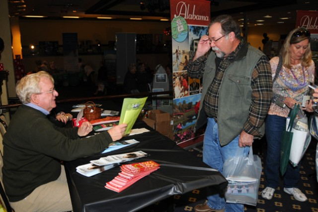 Dennis Nagel, retired military, stops to speak with Brock and Miriam Wells at the Foley, Ala., booth during the 25th annual Travel Extravaganza March 6.