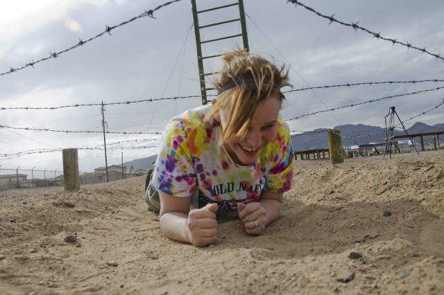 Lindsay Sealy crawls under barbed wire on the Fort Bliss air assault course. This obstacle provided little challenge to the FRG members.