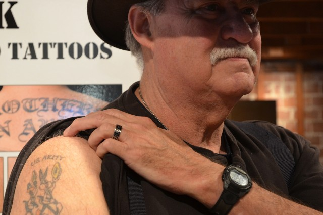 David Hancock displays the tattoo of Daffy Duck and Bugs Bunny on his arm representing his dual-military career in the U.S. Army and U.S. Marines.