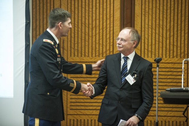 Col. Peter Helmlinger, left, the U.S. Army Corps of Engineers Europe District commander, shakes hands with Ralf Poss, undersecretary for the German Federal Ministry of Transport, Building and Urban Development, at the annual Bauamt Partnering Meeting on Feb. 27 in Freiburg, Germany.