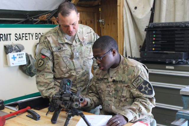 "Sgt. Kasim Kennerly, the non commissioned officer in charge, performs the final weapons inspection while Chief Warrant Officer Gomez looks on. ""I make sure that everything was done accurately,"" said Kennerly. ""I make sure all parts are there, the weapon is functioning properly and that all the paperwork is filled out correctly."""