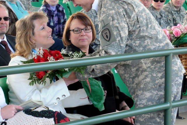 "FORT CARSON, Colo. "" Sherri Woods, wife of outgoing command sergeant major, Michael Woods, 71st Ordnance Group (Explosive Ordnance Disposal), receives a bouquet of red roses during a change of responsibility ceremony at Founders Field, March 7, 2013. (U.S. Army photo by Spc. Nathan Thome, 4th Inf. Div. PAO)"
