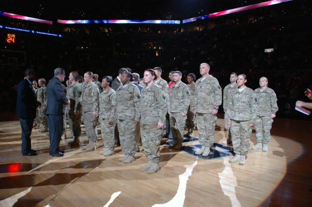 "Soldiers of the 14th Military Intelligence Battalion receive ""challenge coins"" from representatives of USAA. The insurance company sponsored the San Antonio Spurs Military Appreciation Night, March 8, at the AT&T Center in San Antonio. (U.S. Army photo by Gregory Ripps, 470th Military Intelligence Brigade Public Affairs)"
