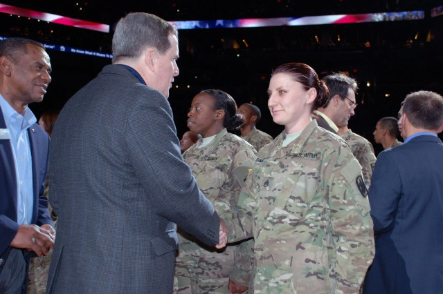 "A representative of USAA presents a ""challenge coin"" to a member of the 14th Military Intelligence Battalion. The insurance company sponsored the San Antonio Spurs Military Appreciation Night, March 8, at the AT&T Center in San Antonio. (U.S. Army photo by Gregory Ripps, 470th Military Intelligence Brigade Public Affairs)"