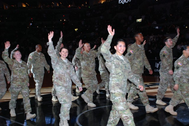 Soldiers of the 14th Military Intelligence Battalion wave to the audience as they leave the playing court of the AT&T Center during halftime at the March 8 NBA game between the San Antonio Spurs and the Portland Trail Blazers. The Soldiers' recognition was part of Military Appreciation Night. (U.S. Army photo by Gregory Ripps, 470th Military Intelligence Brigade Public Affairs)