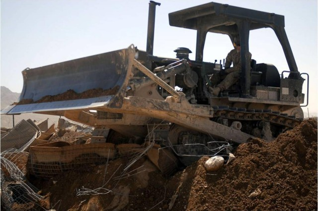 Spc. Joshua Vermote, a motor transport operator and member of the 1-41FA Traveling Transition Team, uses a bulldozer to tear down Hesco barriers as his team begins demilitarization of a Forward Operating Base located in Zabul province, Afghanistan, March 9. The purpose of the T3 is to return southern Afghanistan's land to the way it was prior to inhabitation by International Security Assistance Forces. (U.S. Army Photo by 1st Lt. Vanessa Macekura)