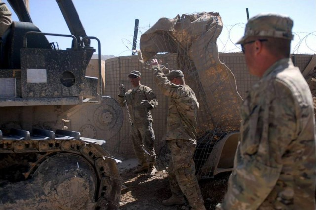 Sgt. Jay Scott, a member of the 1-41FA Traveling Transition Team, ground guides the bulldozer close enough to the debris in order to tow it via chain to the disposal site, as Spc. Wesley Berry and Sgt. 1st Class Marold Mills, watch and wait to begin the hook up, March 9. The purpose of the T3 is to demilitarize and return southern Afghanistan's land back to the way it was prior to International Security Assistance Forces inhabitation. (U.S. Army Photo by 1st Lt. Vanessa Macekura)