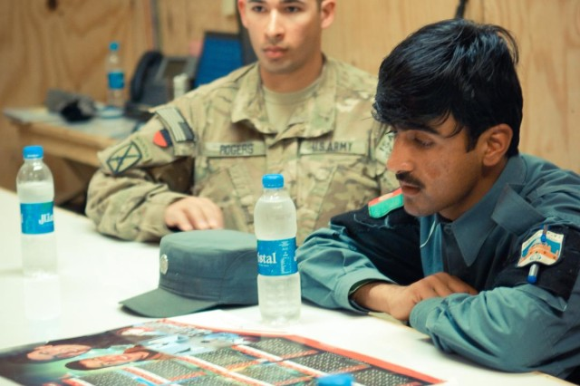 Army 1st Lt. Gerald Rogers, Security Force Assistance Team (SFAT) 20, Combined Task Force (CTF) 4-2, explains how to create a training schedule to Afghan Uniformed Policemen Sgt. Abdulla and Sgt. Noorulah, March 6, Kandahar province, Afghanistan. (U.S. Army photo by 2nd Lt. Jennifer Frazer, 102nd Mobile Public Affairs Detachment)