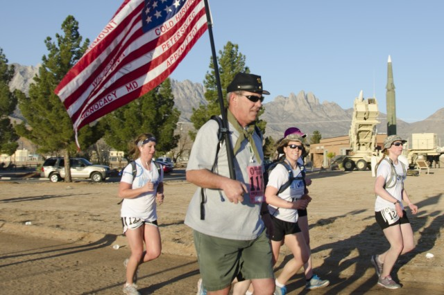 A participant marches with an American flag that names the Civil War Battles at the Bataan Memorial Death March held at White Sands Missile Range, N.M. Nearly 6,000 who endured the desert terrain and high winds during the march, March 17, 2013.