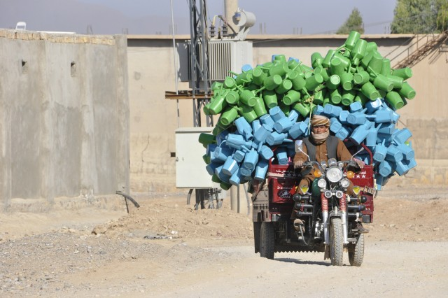 A man transports plastic goods from a factory at the Shur Andam Industrial Park in Kandahar City, Afghanistan. Since 2011, the Kandahar Bridging Solution has provided diesel-powered generators which produce reliable energy at strategic locations, including the industrial park. Consistent and reliable electricity has encouraged economic development in Kandahar.
