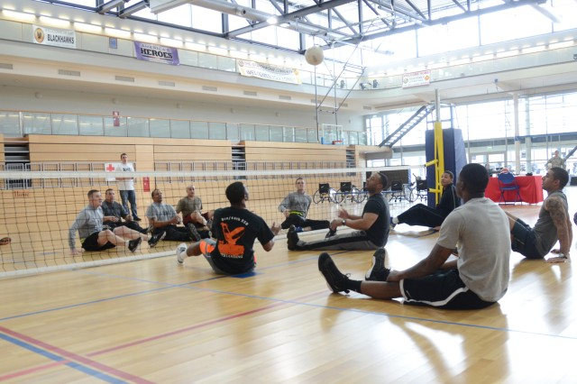 Warrior Transition Battalion-Europe Soldiers (left) square off against Soldiers from the 44th Expeditionary Signal Battalion during a seated volleyball game.