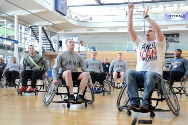 Players watch for the outcome of Pfc. David Hunter's hoop shot during a game of wheelchair basketball.