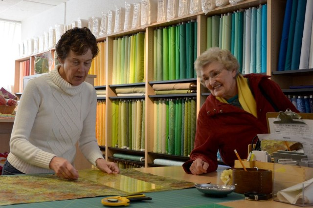 Sandy Vaughn, a volunteer at the new Kaiserslautern Arts and Cultural Center, measures a piece of fabric while talking with customer Ernie Gilgore