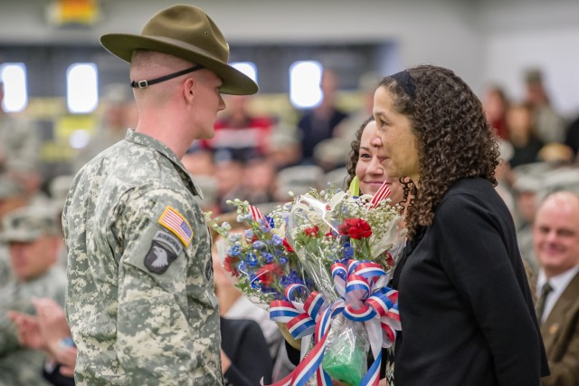 Sgt. 1st Class Adam McQuiston, Fort Leonard Wood's Drill Sergeant of the Year, presents Ann Wells with flowers March 11 during a change of responsibility and retirement ceremony at Nutter Field House. She is credited for being a passionate advocate for military families, a mentor, an active adviser, and supporter of organizations such as the USO, Army Family Action Plan and Fort Wood Community Spouses Club.