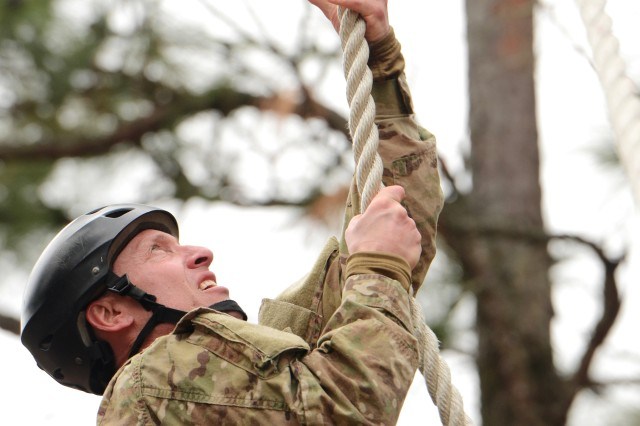 """A Special Forces Soldier with Company C, 4th Battalion, 3rd Special Forces Group (Airborne), climbs a rope on the """"Nasty Nick"""" Obstacle Course on Camp Mackall, N.C., Feb. 25, 2013."""