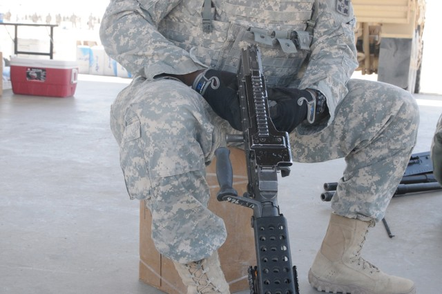 "CAMP BUEHRING, Kuwait. "" Specialist Ashton White, transportation specialist, Company A, 4th Brigade Support Battalion, 1st Armored Brigade Combat Team, 4th Infantry Division, practices assembling and dissembling a M240B Machine Gun, after qualifying with his assigned weapon at Udairi Range, Kuwait, March 12, 2013."