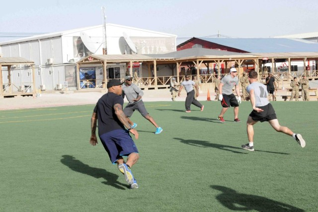 """D'Qwell Jackson, Stevonne Latrall Smith and Justin James """"J.J."""" Watt play football with troops currently stationed in Regional Command-South, Afghanistan, March 18, 2013."""