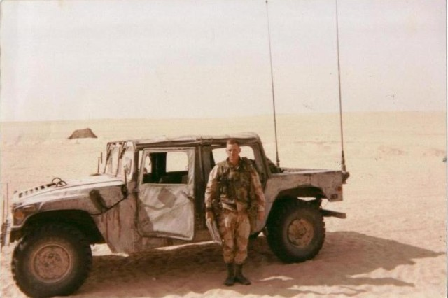 "Robert Fay Sr., an infantryman assigned to Company A, 3rd Battalion, 187th Infantry Regiment, 3rd Brigade Combat Team ""Rakkasans,"" 101st Airborne Division (Air Assault), stands near his Humvee in the desert near Iraq during the Gulf War. Fay Jr. was born and named just after his father was deployed."