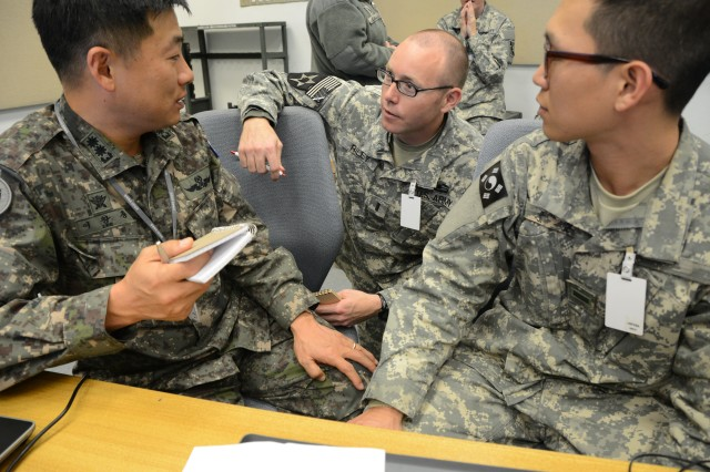 Lt. Col. Chang Jung Lee (left), Republic of Korea Army Headquarters Liaison Officer to U.S. Army Service Component Command FWD (ASCC FWD) speaks with 1Lt. Benjamin Riley, 405th Civil Affairs Battalion, U.S. Army reserve, with the assistance of Pvt. 1st Class Joon Hyoung Kim, a Korean Augment to the U.S. Army (KATUSA) during exercise Key Resolve in Daegu, Korea March 14, 2013.  ASCC (FWD) consists primarily of Soldiers from the U.S. Army Pacific Contingency Command Post from Fort Shafter, HI, along with augmenting forces from active duty and reserve units from the U.S. Key Resolve is a combined-joint command post exercise designed to help improve theater operations performance capabilities of the RoK-U.S. combined defense system, test the ability of augmenting forces deployment into the Korean peninsula and maintain the RoK war-fighting capability in order to defend the Korean Peninsula.  Key Resolve 2013 is being led for the first time by the RoK Joint Chiefs of Staff and 10,000 RoK and 3,500 U.S. servicemembers are participating in the exercise held annually in Korea around the same time every year.  The RoK JCS led exercise is being used to establish the basis for the transition of wartime operational control to the RoK.