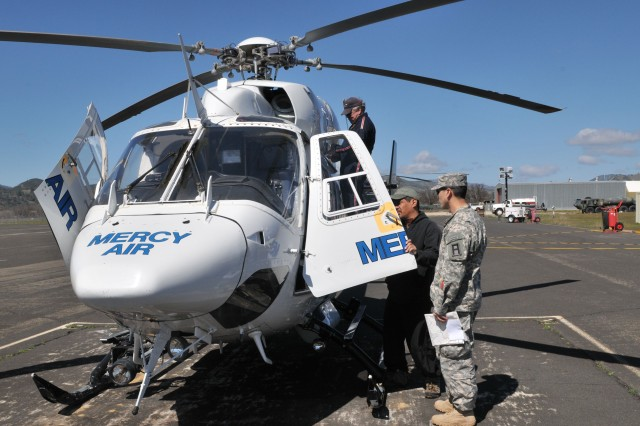 Capt. Forrest Ryan, right, Headquarters and Headquarters Company, 191st Infantry Brigade, Division West, receives a safety briefing from a Mercy Air air ambulance crew member prior to aerial reconnaissance at Fort Hunter Liggett, Calif., March 9. In addition to providing normal emergency medical support at the installation, Mercy Air crews are acting as role players for medical evacuation exercises conducted during the 189th Infantry Brigade's Task Force Cold Steel training mission. (Photo by Sgt. Jeran Placke, 189th Infantry Brigade, Division West, Public Affairs)