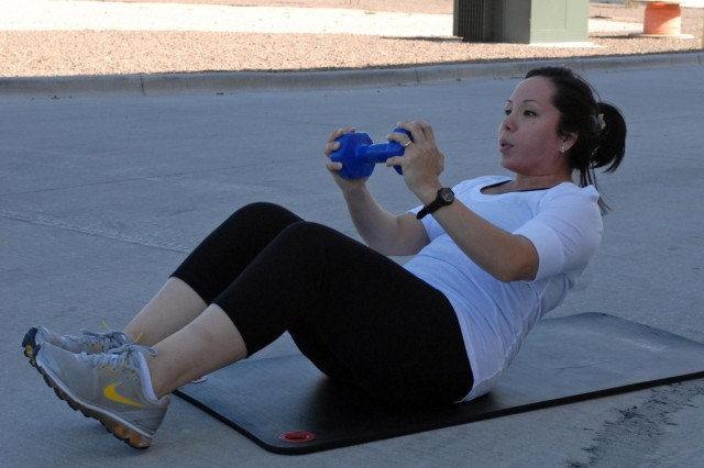 Melissa Zamora, a military spouse from Nogales, Ariz., performs crunches while holding a 10-pound dumbbell during a Stroller off Stress class at the Soto Physical Fitness Facility on East Fort Bliss, Sept. 17. U.S. Army photo by: Sgt. Terence Ewings, 24th Press Camp Headquarters.