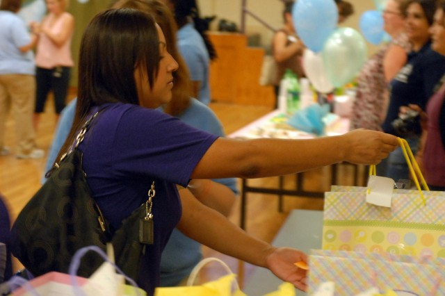 Malu Brooks, a student attending the Western Technical College in El Paso, Texas, places a gift bag, filled with baby goods, on the donation table during a community baby shower hosted by the Fort Bliss Army Volunteer Corps at the Army Community Service Center, Sept. 6. Brooks, a native of San Fernando, Calif., is the President of the Technology Education Attendance Management Students (T.E.A.M.S.) Committee, which regularly volunteers on Fort Bliss and around the El Paso, Texas.