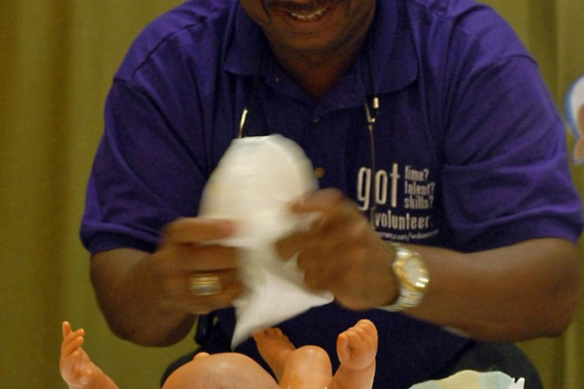 Anthony Lovett, Chief of Operations at the Fort Bliss Army Community Service Center, races to put a diaper on a baby doll in a Diaper Dash competition during a community baby shower hosted by the Fort Bliss Army Volunteer Corps at ACS, Sept. 6. Lovett, a native of Tampa, Fla., who is responsible for overseeing the operations at ACS, supported the installation' Army Volunteer Corps program by participating in the games during the event and donating baby goods, which will be used to help stock the shelves of the installation' Junior Enlisted Family Center and other El Paso community nonprofit agencies.